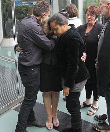 Phillip Cottrell's sister, Sue Hollows, is comforted by her husband, Heath Hollows, and a family friend outside the High Court