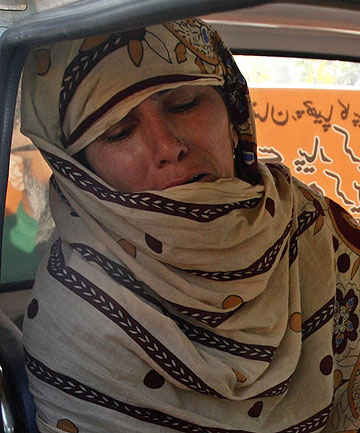 MOTHER GRIEVES: Rukhsana Bibi cries while sitting next to the body of her daughter Madiha, a worker of an anti-polio drive campaign, in an ambulance outside Jinnah Hospital in Karachi.
