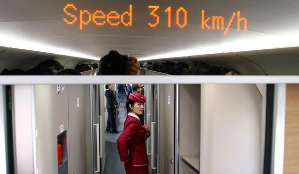 An attendant stands inside a high-speed train during an organised experience trip from Beijing to Zhengzhou, as part of the new rail line.