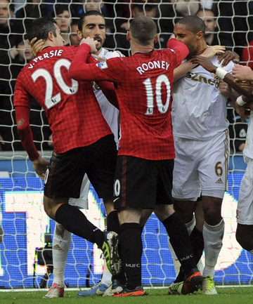 Swansea City's Ashley Williams is separated by Manchester United's Wayne Rooney (10) after a foul on Robin Van Persie (left) during their English Premier League match at the Liberty Stadium in Swansea.