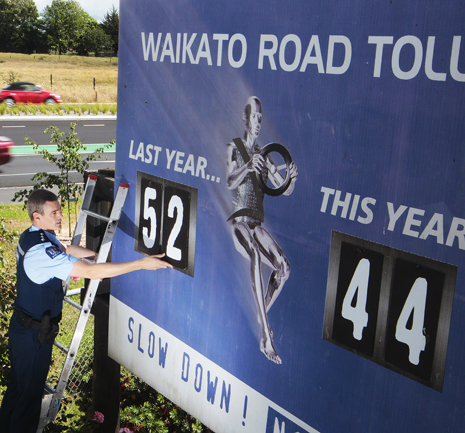 Waikato district road policing manager Inspector Marcus Lynam adjusts Waikato's road toll just hours before another person died on the region's roads yesterday. The sign compares this year's toll to the same date last year.
