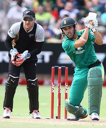 South Africa's Farhaan Behardien drives as New Zealand's Brendon McCullum of New Zealand watches from behind th