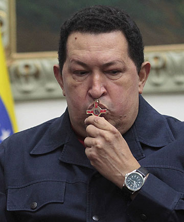 CANCER FIGHT: Venezuelan President Hugo Chavez kisses a crucifix as he speaks during a national broadcast at Miraflores Palace in Caracas.