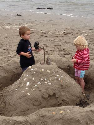 Connor, 4, and Caitlin, 2, add the finishing touches to their entry for Whangamata's Big Sandcastle Competition.