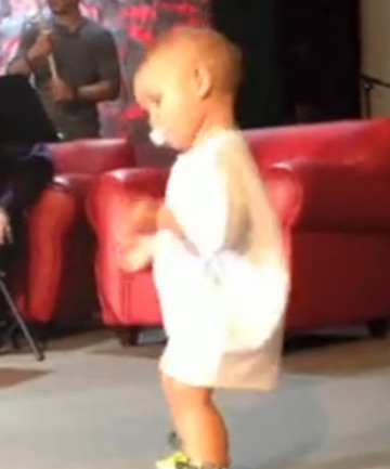 Baby crashes dad's concert with his dancing moves.