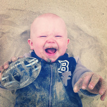 Ten month old Levi Adams enjoys some footy and sand on 90mile beach, Northland.