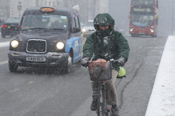 A cyclist crosses Westminster bridge in the snow in central London.