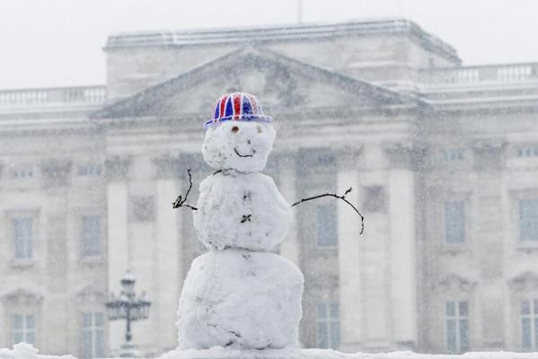 A snow man wearing a Union flag hat is seen in front of B