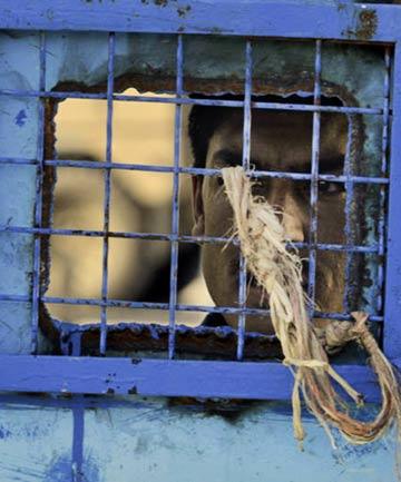 A prisoner looks out of his cell window at the main prison in Kandahar, Afghanistan.