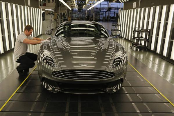 An Aston Martin Vanquish is inspected by hand inside a light booth by technician Matthew Goss at the company headquarters and production plant in Gaydon, England.