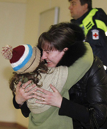 HOME AGAIN: A woman hugs her daughter, who was a passenger on a Russian Emergencies Ministry flight from Beirut, after her arrival at Moscow's Domodedovo airport.