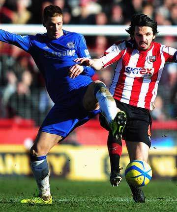 Chelsea's Fernando Torres (left) and Brentford's Jonathan Douglas challenge for the ball during the FA Cup fourth round match between  at Griffin Park.