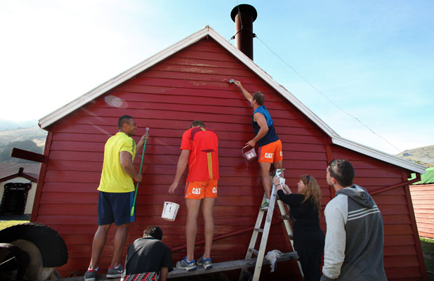 Robbie Fruean, Dominic Bird and Andy Ellis of the Crusaders help paint the museum near Okains Bay.