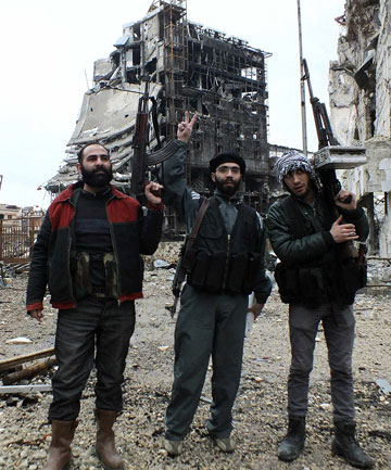 REDUCED TO RUBBLE: Free Syrian Army fighters carrying weapons pose in front of destroyed buildings in Homs.