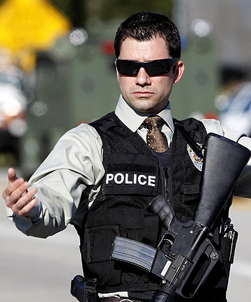 An armed police officer directs and stops traffic during the manhunt for fugitive former Los Angeles police officer Christopher Do