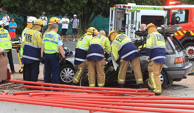 Fire rescue personnel work to free a man trapped in his car after a collision in Hamilton.