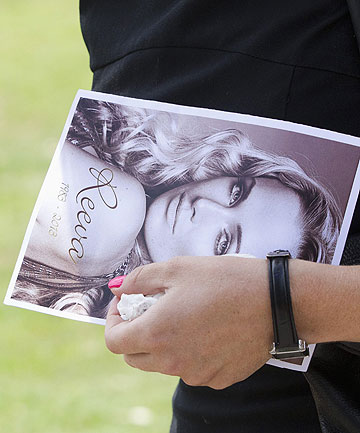 'WAS IT TO KILL HER, OR WAS IT TO GET HER OUT?: A mourner leaves, holding a picture