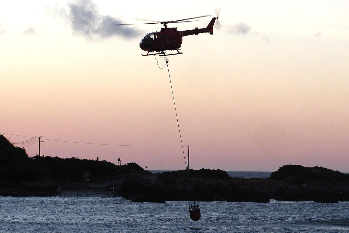 A helicopter refills its monsoon bucket in Ohiro Bay.