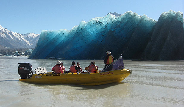 Tourists with Glacier Explorers face to face with the largest ever iceberg to calve off the face of the glacier into the Tasman Glacier Terminal Lake.