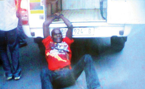 A South African police vehicle drives off with a 27-year-old taxi driver from Mozambique handcuffed to the back.
