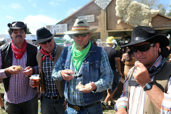 Food Cowboys trying barbequed mountain oysters trying at the Hokitika Wildfoods Festival.