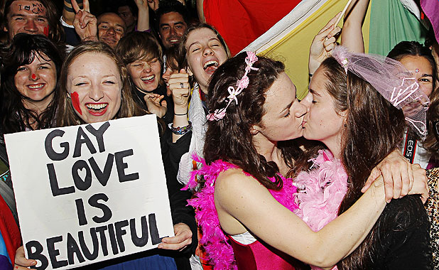 LOVING SUPPORT: Rosie Jimson-Henley holds a sign as Emma Fawcett and Phillipa Walker kiss during a rally outside Parliament as the Marriage (Definition of Marriage) Amendment Bill is debated inside.