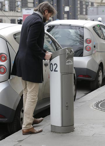 A man charges up a Paris Autolib' electric car at a parking station in Paris.
