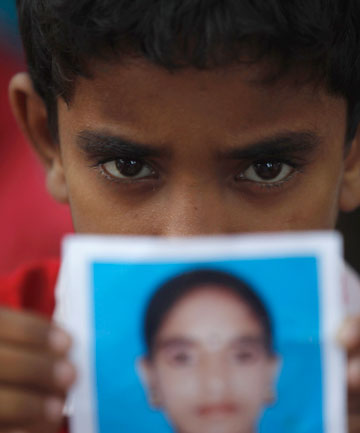 A boy holds a picture as he waits for news on his sister, a garment worker who is still missing, after the collapse of the Rana Plaza building