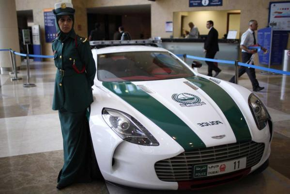 A police officer stands near an Aston Martin car used by Dubai police, during the Arabian Travel Market exhibition in Dubai.