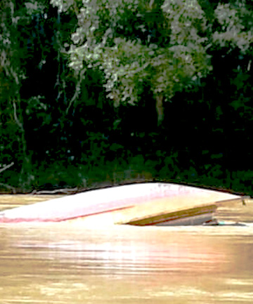 A capsized boat floats in a river of Sungai Rajang in Belaga
