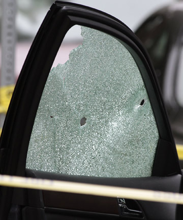 A vehicle sits on the side of a road with a window shattered by bullets in the incident that left six people dead in Santa Monica, California.