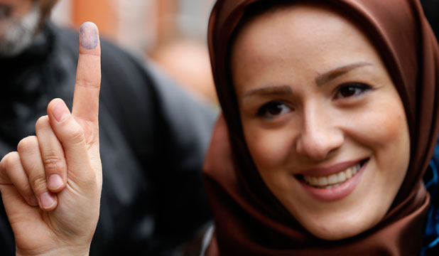 Voter Zeynab shows the ink stain on her finger, to prove that she has voted, outside the Iranian consulate in central London June 14, 2013.