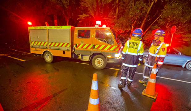 Fire Service members cordon off Titirangi Beach Road in West Auckland after a large landslide into a house caused an evacuation of its occupants.