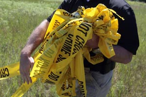 A US investigator carries yellow crime tape at a field where a search was conducted for the remains of former Teamsters boss Jimmy Hoffa in Oakland Township, Michigan.