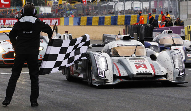 Denmark's Tom Kristensen, driving the Audi R18 E-Tron Quattro, crosses the finish line to win the Le Mans 24-hour sportscar race.