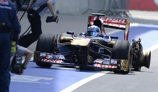 Toro Rosso Formula One driver Jean-Eric Vergne of France enters the pit with a punctured tyre during the British Grand Prix at the Silverstone.