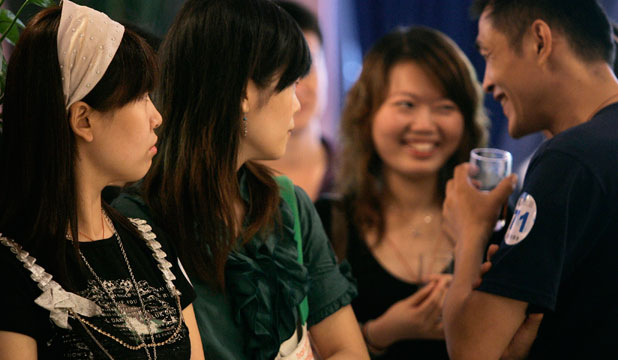 wo women watch as a couple laugh together at a matchmaking party organized by a Chinese website on
