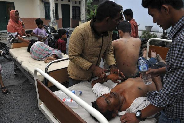 Injured residents receive treatment outside the local clinic after the quake.