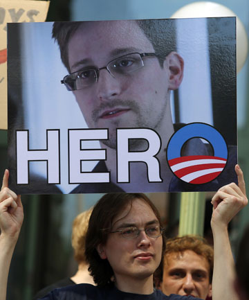 A demonstrator holds a sign with a photograph of former U.S. spy agency NSA contractor Edward Snowden during Fourth of July Independence Day celebrations in Boston, M