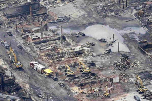 Workers and firefighters work around the remains of downtown Lac Megantic after a driverless, runaway fuel train exploded in a deadly ball of flames in the centre of the small Quebec town.