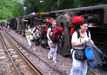 Passengers carry their belongings as they leave a derailed train in northern Thailand.