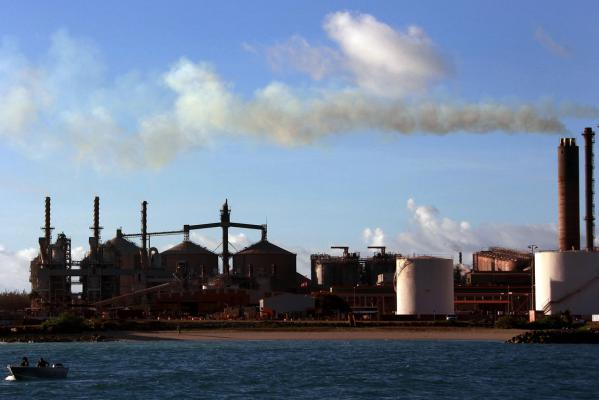 A boat is seen in front of chimneys billowing smoke at the Rio Tinto alumina refinery in Gove, also known as Nhulunbuy, located 650 kilometres east of Darwin in Australia's Northern Territory.