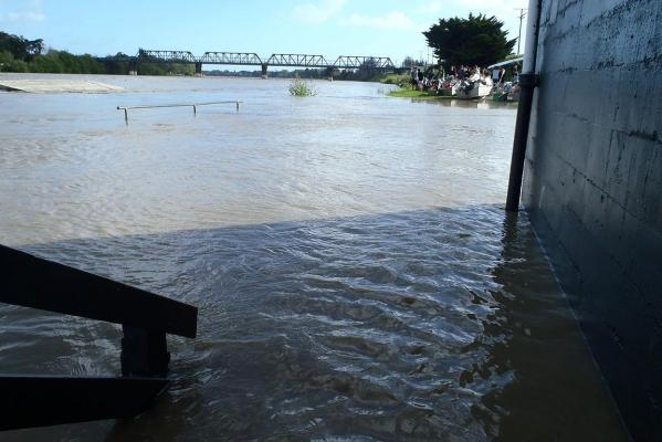 Aramoho Wanganui Rowing Club's pontoon under water as boats are moved out of the shed.