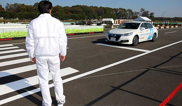 Honda's electronically-operated car halts on its own to allow a pedestrian to cross.