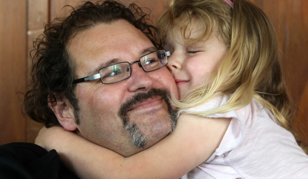 Danny Bedingfield receives a cuddle from his 4-year-old daughter, Ella.