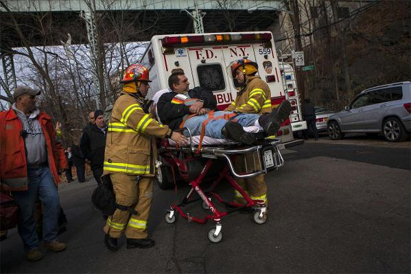 Emergency personnel evacuate a victim from the scene of a Metro-North train derailment in the Bronx.