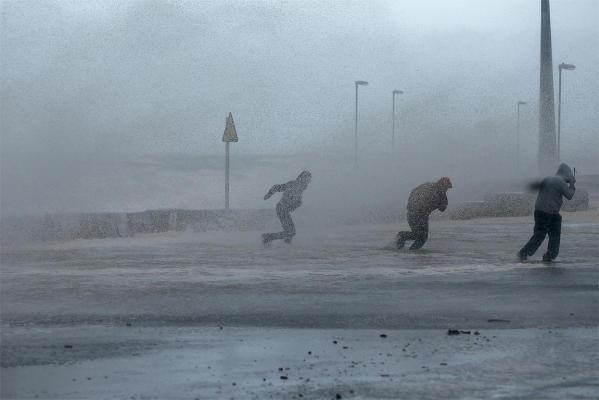 People run through sea spray in Rhyl, north Wales, as the storm hits.
