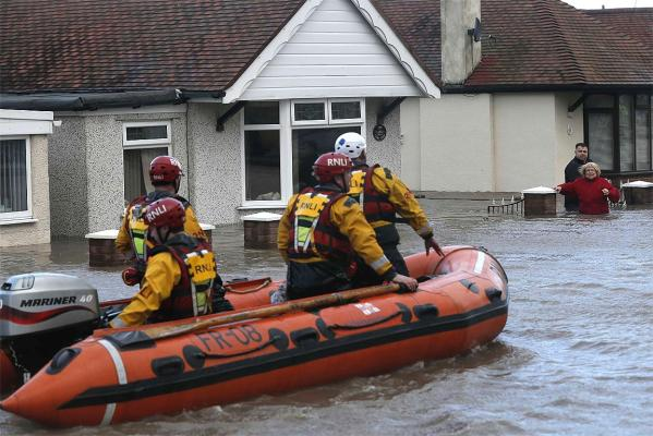 Emergency rescue service workers in an inflatable boat evacuate residents from flood waters in a residential street in Rhyl, north Wales.