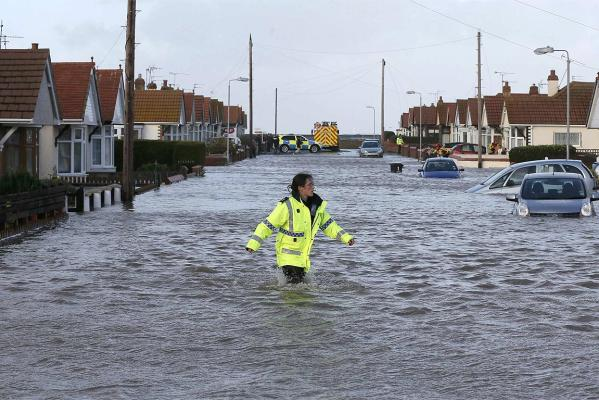 An emergency rescue service worker walks through flood water in a residential street in Rhyl, north Wales.