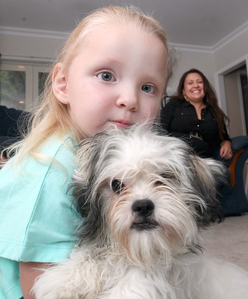 Two-year-old Savannah Copeland  holds Popy the dog